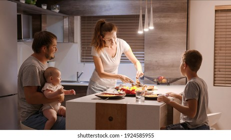 In the Kitchen: Family of Four having supper Together. Mother, Father, Boy and little Girl enjoying feast at home.