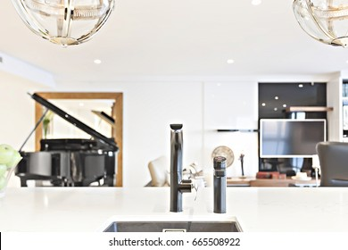 Kitchen faucet focusing on the white counter top with blurred background with white walls, a piano and a television can be seen blurred from the behind