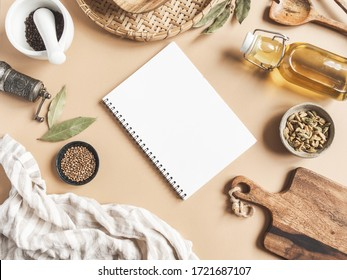 Kitchen flat lay with open notebook for culinary text and small bowls various dry spices, wood kitchen utensils, olive oil in glass bottle on a beige background. Top view. copy space