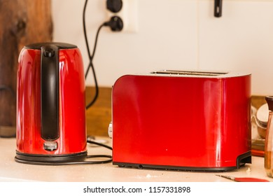 Kitchen furniture concept. Red boiling pot and toster on table next to electric socket
