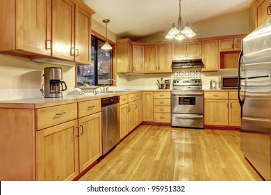 Kitchen with golden wood  cabinets and hardwood floor. Simple American home.