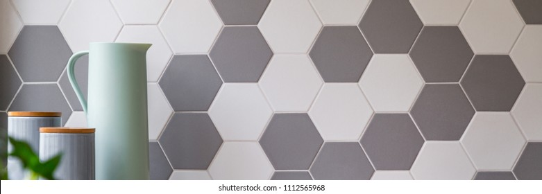 Kitchen with grey and white honeycomb wall tiles and stylish food containers, panorama
