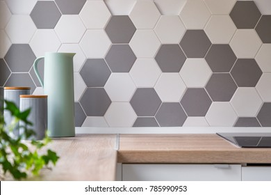 Kitchen with grey and white honeycomb wall tiles and wooden worktop,