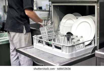 Kitchen hand with an open dishwasher filled with clean white plates in a restaurant kitchen in a catering and hygiene concept
