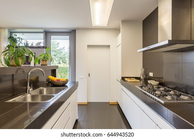 Kitchen interior with the aisle between two worktops, silver sink and amenities