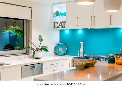 Kitchen interior with colourful decor and blue glass splashback. Modern kitchen interior close up. Photographed: February, 2018.