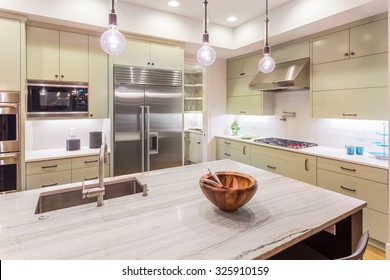 Kitchen Interior Detail with Island, Sink, Cabinets, and Hardwood Floors in New Luxury Home