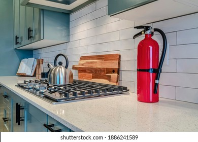 Kitchen interior with fire extinguisher and cooking unit on the white countertop