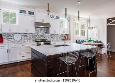 Kitchen interior with island, sink, cabinets, hardwood floors in luxury home.