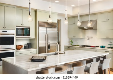 Kitchen Interior with Island, Sink, Cabinets, Stainless Steel Refrigerator, Oven, and Hardwood Floors in New Luxury Home