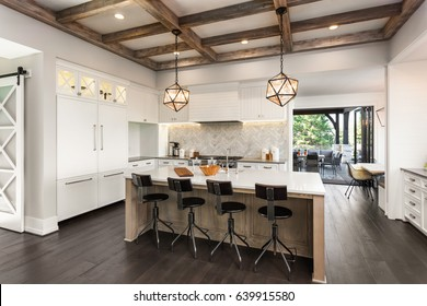 Kitchen Interior with Island, Sink, Cabinets, and Hardwood Floors in New Luxury Home. Features Open Sliding Glass Doors that Lead to Outdoor Patio, Elegant Pendant Lights, and Built-in Refrigerator