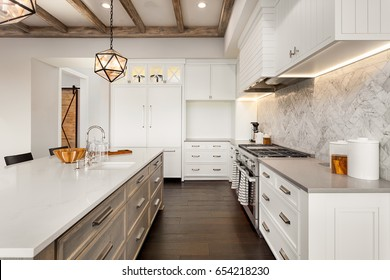 Kitchen Interior with Island, Sink, Cabinets, Pendant Light Fixture, and Hardwood Floors in New Luxury Home.  Island Boasts Large Number of Drawers; Herringbone Tile Backsplash Enhances Elegant Design
