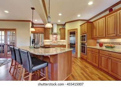 Kitchen interior with island. Wooden cabinets with granite counter top and hardwood floor