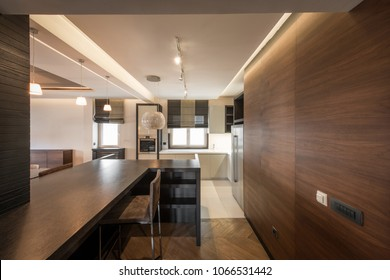 Kitchen interior in luxury apartment with brown wooden wall and counter