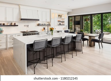 Kitchen interior in new luxury home with hardwood floors, waterfall island, dining room table. Covered patio is visible through glass accordion style doors.