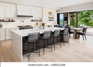 Kitchen interior in new luxury home with hardwood floors, waterfall island, dining room table, and accordion style glass doors. Glass doors are open showing exterior patio