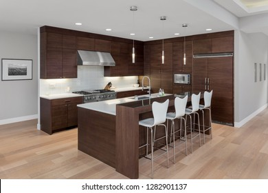 Kitchen Interior in New Luxury Home. Features Large Island, Stainless Steel Appliances, Dark Hardwood Cabinets and Hardwood Floors