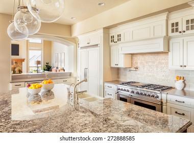 Nội thất nhà bếp tại New Luxury Home với đảo, bồn rửa, tủ và sàn gỗ cứng
