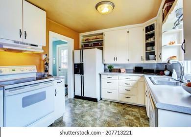 Kitchen interior in old house. View of white cabinets with white appliances.