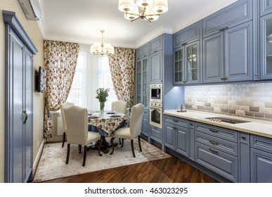 Kitchen interior with served for a dining table for four persons, and the window curtains.