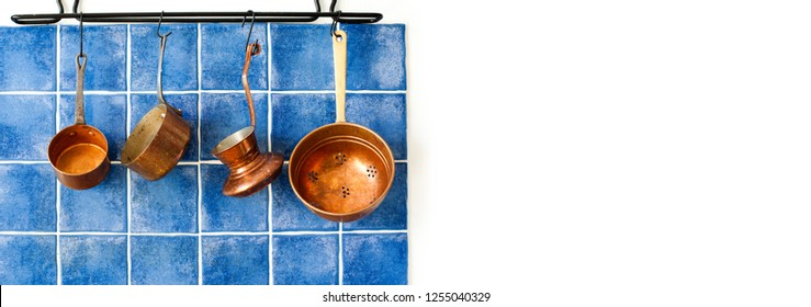 Kitchen interior with vintage copper utensils. old style cookware kitchenware set. Pots and coffee maker hanging on blue tile wall. Copy space, white background.