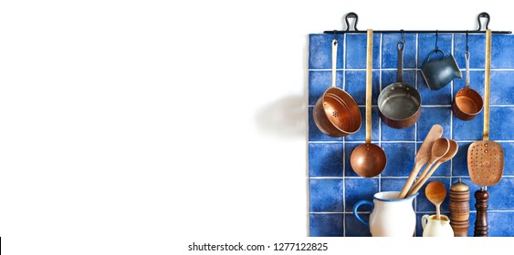 Kitchen interior with vintage copper utensils. old style cookware kitchenware set. Pots, kitchen spoon, skimmer hanging on blue tile wall. Copy space, white background.