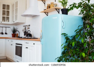 Kitchen interior in white textured colors with blue modern retro fridge and rustic brick wall