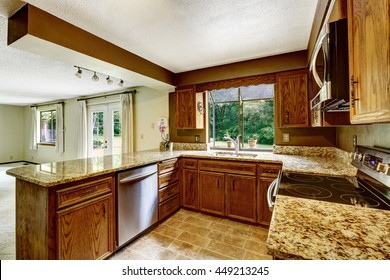 Kitchen interior with wooden cabinets, tile floor and granite counter top