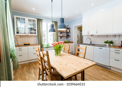 kitchen interior with wooden kitchen table and a bunch of tulips