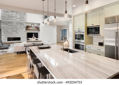 Kitchen with Island, Sink, Cabinets, and Hardwood Floors