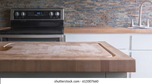 Kitchen Island wood butcher block top with stove, sink and counter in background