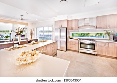 Kitchen items with modern furnitures and walls, ceramic cups also fruits on the table, floor is tiled, flower vase next to gas cooker, perfect lightning.