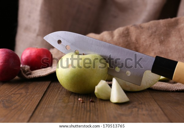 Kitchen knife and apples,   on wooden background