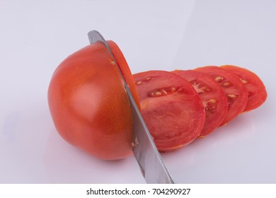 Kitchen knife sliced tomato on white background