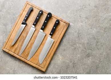 Kitchen knives set laying on wooden cutting board, flat lay, view from above, space for a text