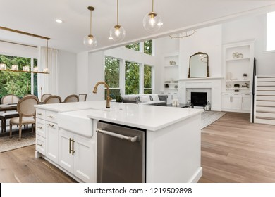 Kitchen and living room in new luxury home. Features kitchen island, dining room with table and chairs, and living room with elegant fireplace.
