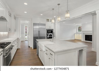 Kitchen and Living Room in New Luxury Home with Hardwood Floors, Farmhouse Sink, Stainless Steel Refrigerator, and Built-Ins with Backlight.