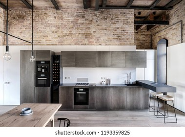 Kitchen in a loft style with brick walls, wooden ceiling and a parquet on the floor. There is wooden table, metal lockers, fridges, stove, oven, sink, dark tabletop, bar chairs, coffee machine.