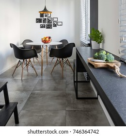 Kitchen with long, granite countertop, concrete floor tiles and round table and chairs