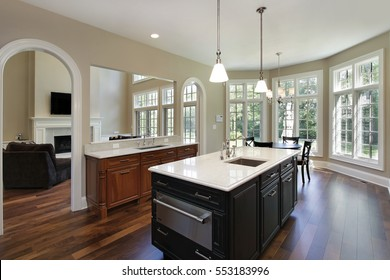 Kitchen in luxury home with oval doorways to family room.
