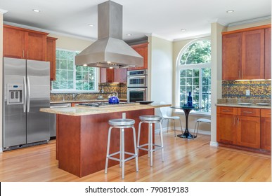 Kitchen in luxury home with stainless steel appliances, granite work surfaces, bar stools and wooden floor.