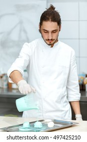 Kitchen magic. Vertical shot of a handsome professional cook decorating desserts with minty blue icing