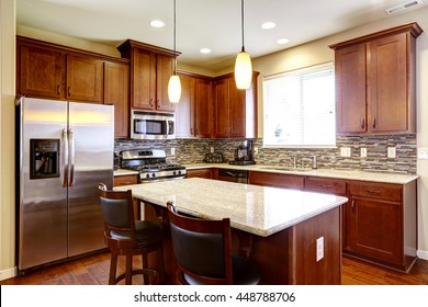 Kitchen mahogany storage combination with steel kitchen appliances, pendant lights and back splash trim.