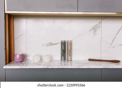 Kitchen marble bench close up with two candles and salt bottles or decor stones.