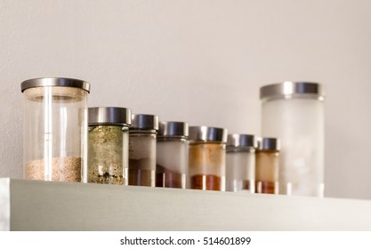 Kitchen metal shelf and glass jars with various spices on white wall