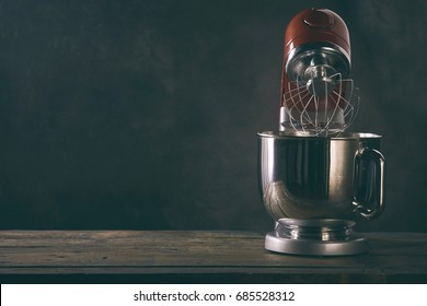 Kitchen mixer standing on wooden countertop against dark background