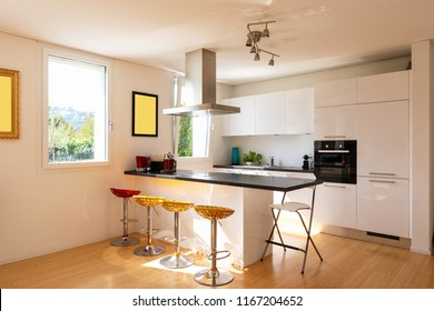 Kitchen in modern apartment with island and stools. Nobody inside