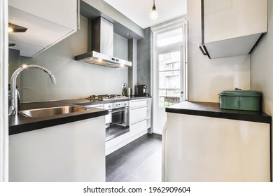 Kitchen with modern furniture and appliances near balcony door at daytime in light apartment