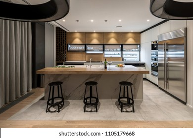 Kitchen in a modern style with light walls and a parquet and tiles on a floor. There are lockers, shelves with dishes and bottles, kitchen island, chairs, chrome fridge, oven, stove, luminous lamps.