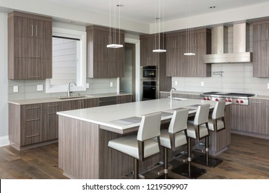 Kitchen in New Luxury Home with dark cabinets and woodwork, and stainless steel appliances